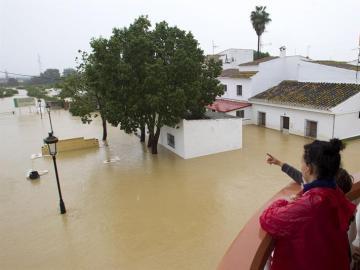 Varias personas observan el estado de sus casas inundadas en la barriada Doña Ana de la localidad de Cártama por las fuertes lluvia caídas esta noche