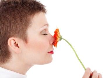 Una mujer huele una flor