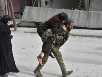 Un soldado sirio trasladando a una mujer herida en Alepo
