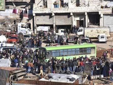 Civiles, combatientes y sus familiares accediendo a uno de los autobuses durante los trabajos de evacuación de los barrios rebeldes de Alepo