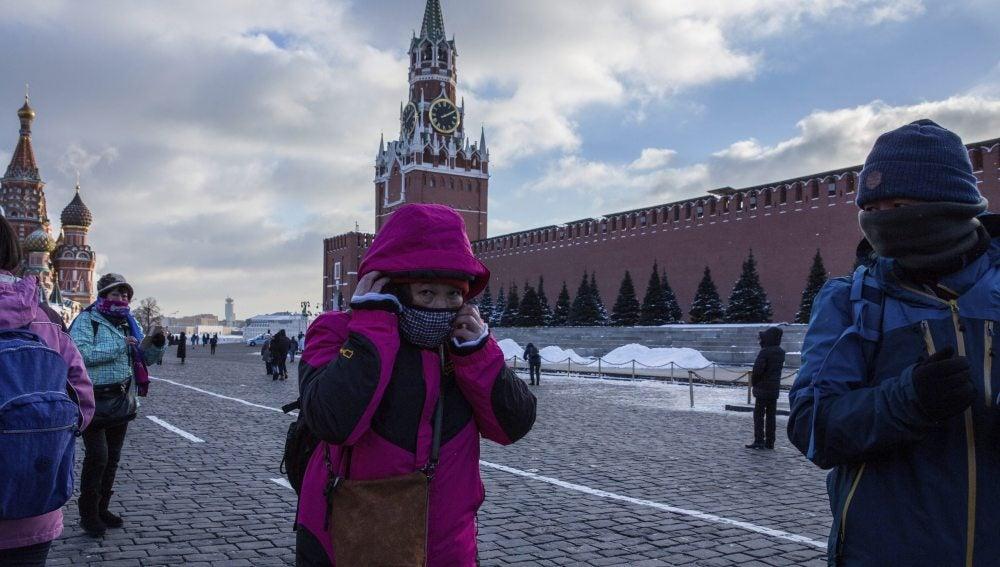 Turistas se abrigan con bufandas durante una visita a la Plaza Roja de Moscú