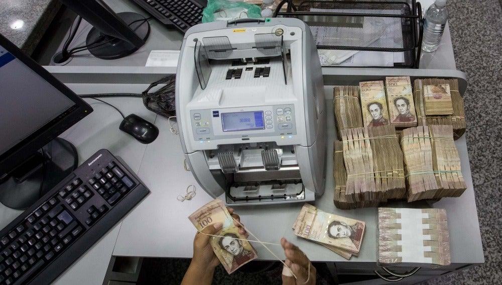 Trabajadoras de un banco cuentan billetes de 100 Bolívares en Caracas (Venezuela)