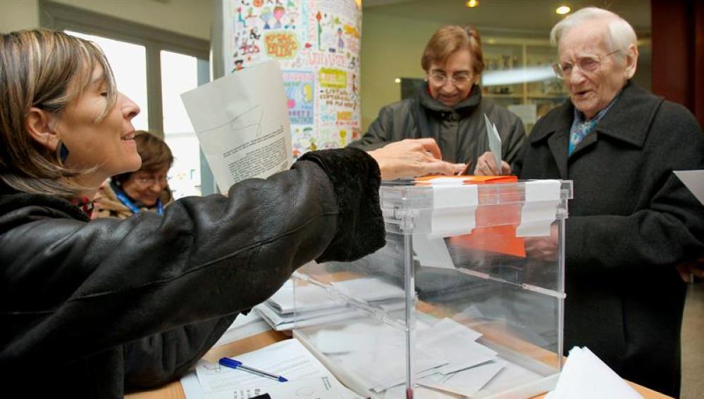 Un hombre deposita su papeleta en la urna de una de las mesas instaladas en un colegio electoral del barrio del eixample barcelonés