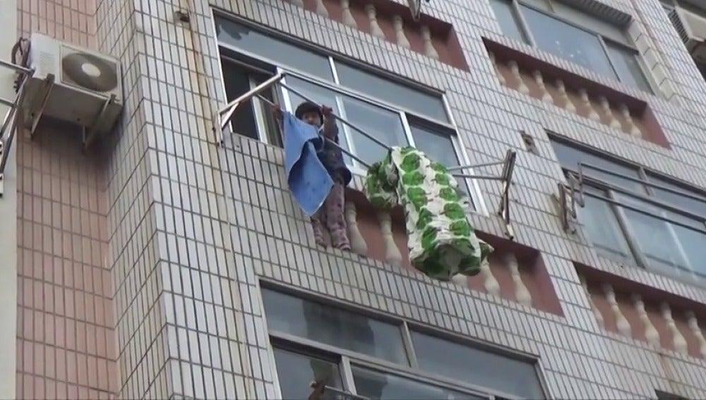 Frame 3.363555 de: Los bomberos salvan a una niña que colgaba de un tendedero en un tercer piso, en China