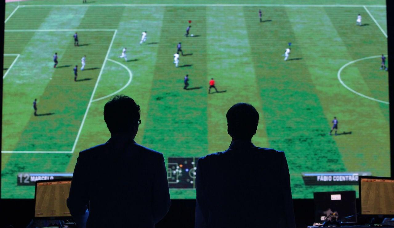 Dos hombres observan un partido del FIFA durante una competición de eSports