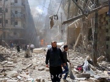 Un hombre camina sobre los escombros de un bombardeo