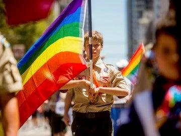 Un Boy Scout portando una bandera gay