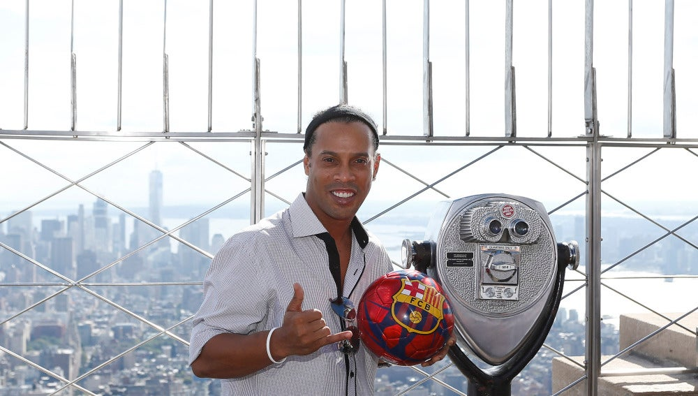 Ronaldinho posa con un balón del Barcelona en el Empire State
