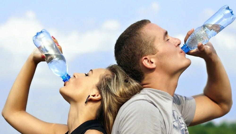 Una pareja bebe agua para hidratarse