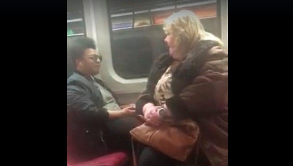 Una usuaria se sienta sobre los pies de este joven en el metro