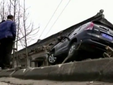 Frame 10.985318 de: Un coche aterriza en el tejado de una casa y el conductor resulta ileso