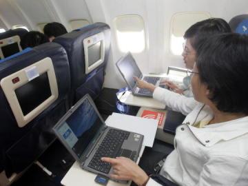 Dos pasajeros utilizando el ordenador portátil en un vuelo