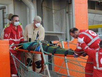 Varios miembros de la Cruz Roja italiana desembarcan a un migrante herido en Palermo, Sicilia