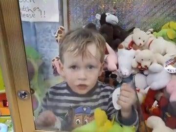 Frame 20.262222 de: Un niño se introduce en una máquina de juguetes para obtener un peluche