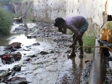 Un hombre bebe agua de una manguera conectada a la fuga de un oleoducto en Nueva Delhi