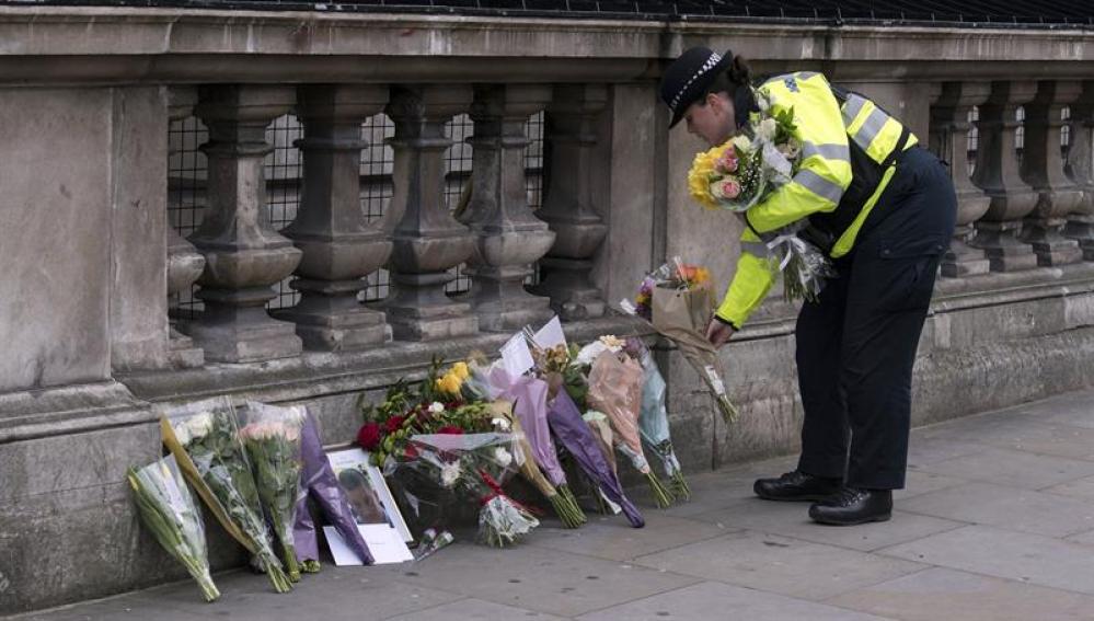 Una agente de la Policía deposita flores cerca del Parlamento