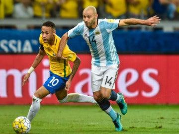 Mascherano peleando un balón con Neymar