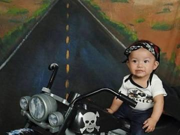 Un bebé con tacones subido a una moto