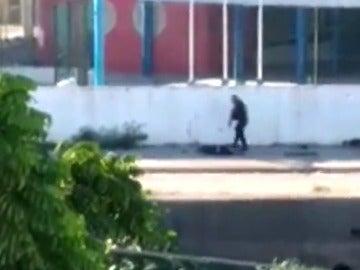 Frame 29.69763 de: Graban a dos policías brasileños asesinando a dos hombres tirados en el suelo junto a un colegio