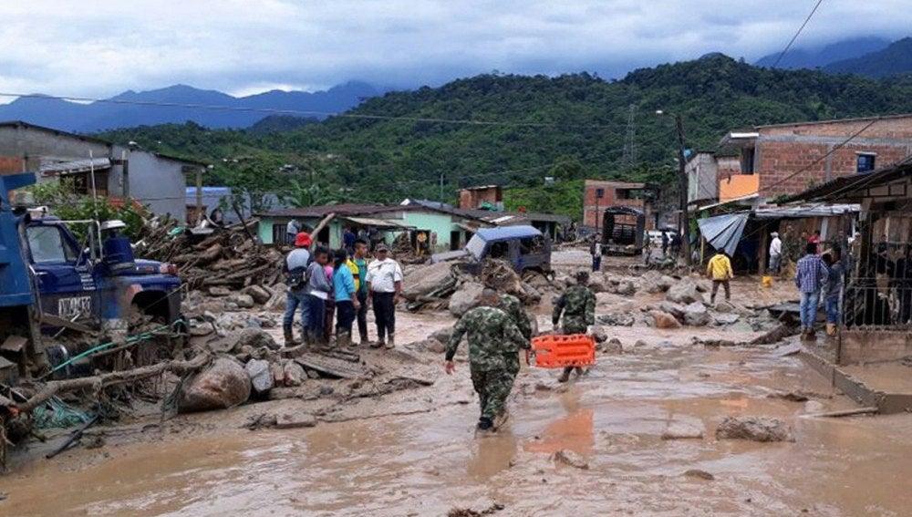 Fotografía cedida por el Ejército de Colombia de sus integrantes ayudando a pobladores por los estragos ocasionados por una avalancha