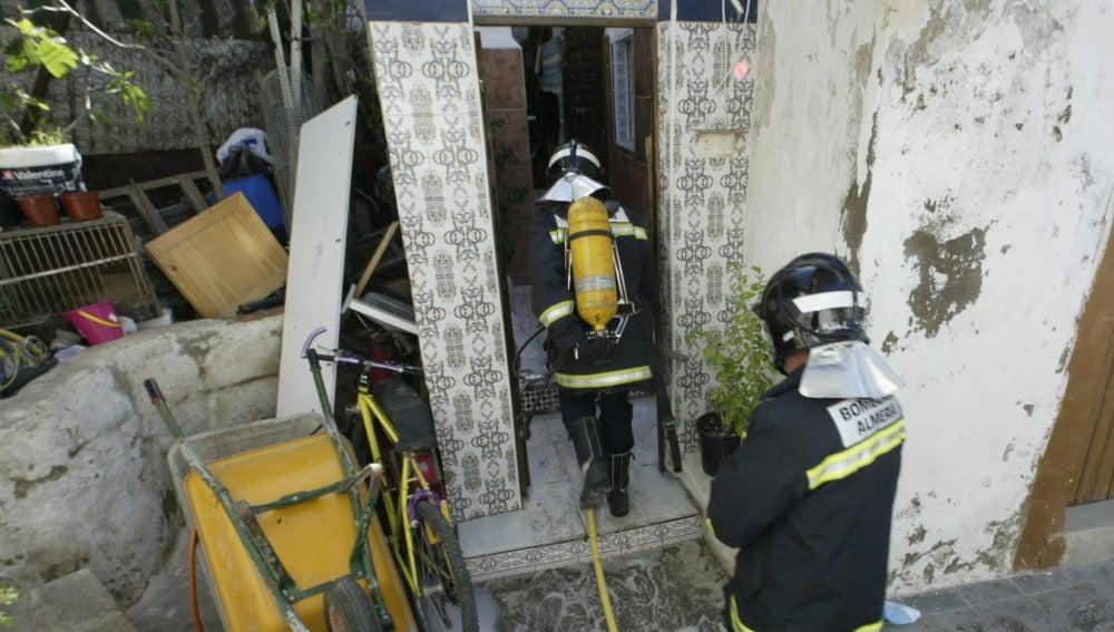 Dos bomberos trabajan en la extinción de un incendio en una casa cueva