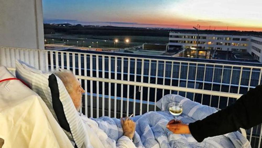 Anciano disfuta de una copa de vino y un cigarro