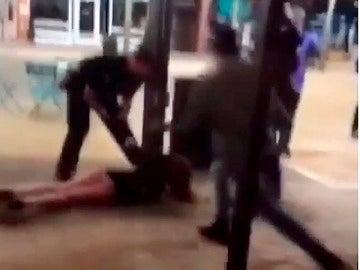 Un policía tumba a una joven en el suelo en plena calle