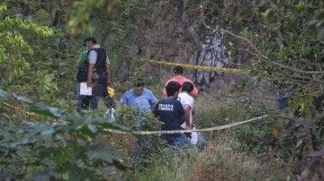 Policías federales y personal médico forense inspeccionan el canal de aguas pluviales