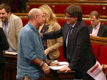 El presidente de la Generalitat, Carles Puigdemont, conversa con el diputado de JxS, Lluís Llach