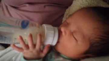 Un bebé sostiene su biberón sin ayuda