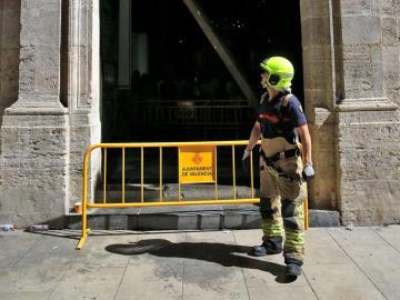 Un bombero observa la puerta de la Basílica de Valencia que se ha descolgado