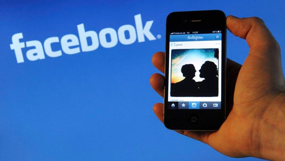 Un iPhone 4 frente al logo de Facebook en un ordenador