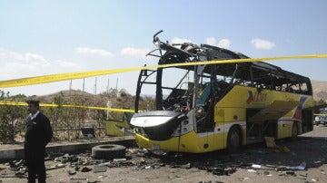 Un policía egipto hace guardia junto al autobús que sufrió un atentado