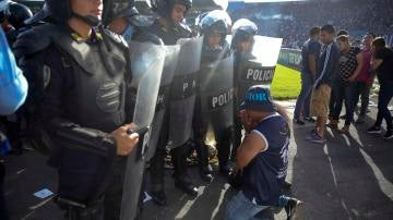Un aficionado se arrodilla ante la policía en Honduras