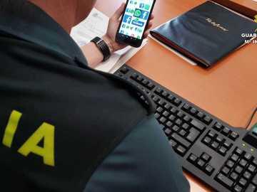 Un agente de la Guardica Civil con un teléfono móvil con acceso a redes sociales