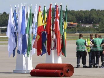 Unos operarios esperan junto a banderas y alfombras rojas preparadas en el aeropuerto para la llegada de los líderes
