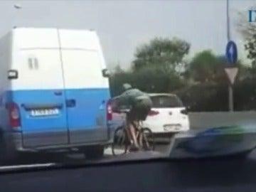 Un ciclista circula, a más de 100 kilómetros por hora, agarrado a una furgoneta