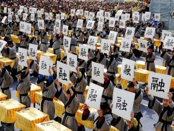 Varias personas sujetan un papel con letras chinas