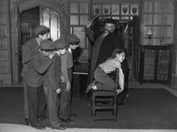 Castigo a un niño con una regla de madera
