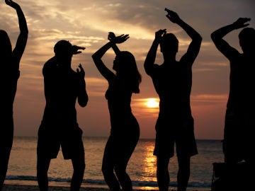 Siluetas de gente bailando en la playa
