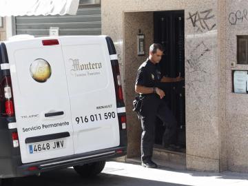 Un agente de la Policía Nacional junto a una furgoneta de los servicios funerarios en el domicilio de la mujer fallecida en Alcorcón