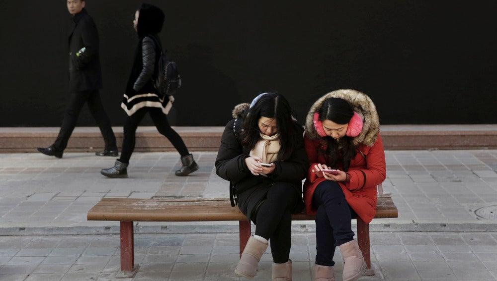 Mujeres chinas mirando su móvil