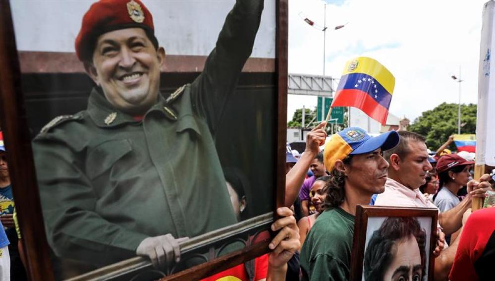 Chavistas participan en una manifestación con un cuadro del fallecido presidente Hugo Chávez