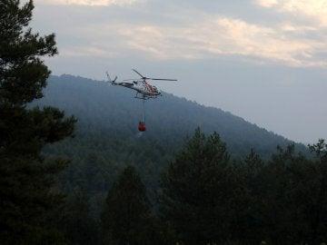 Un helicóptero trabaja en las labores de extinción del incendio forestal declarado en el municipio de Artés (Barcelona)