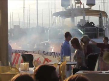 Activistas antisistema se plantan ante un restaurante del puerto de Palma con bengalas