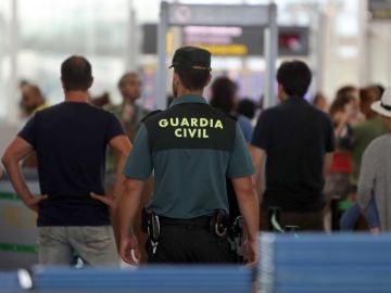 Agentes de la Guardia Civil custodian los accesos a las puertas de embarque en el aeropuerto de Barcelona
