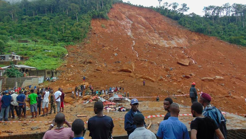Reisdentes de la zona observan los daños causados por un deslizamiento de tierra en  Regent en Freetown, Sierra Leona.