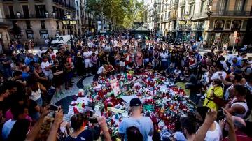 Locales y turistas, rodeando el mítico mural de Miró donde ocurrió la matanza, emocionados