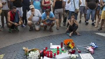 Varias personas se paran frente al mosaico de Miró en las Ramblas de Barcelona