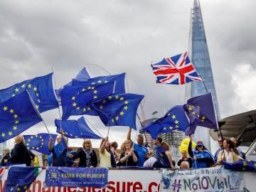 Varias personas con banderas de la Unión Europea protestan contra el brexit en un barco por el río Támesis, en Londres